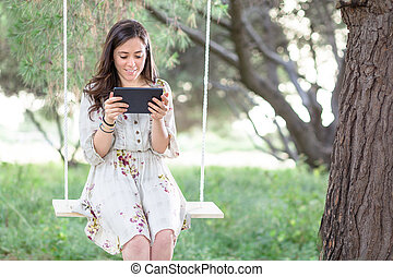 Woman with Tablet on a Swing