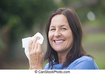 Portrait smiling attractive mature woman suffering from cold or flu infection, sneezing into tissue, painful seasonal hayfever, with blurred outdoor background and copy space.