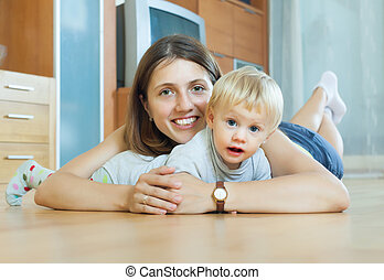 smiling  woman with toddler on  wooden floor