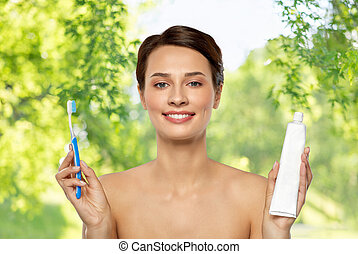 smiling woman with toothbrush cleaning teeth