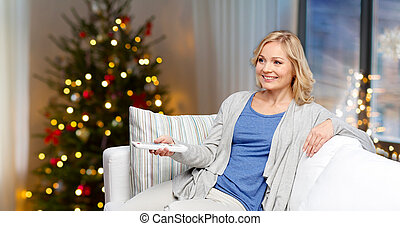 smiling woman with tv remote at home on christmas