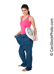 Smiling Woman With Weight Scale Showing Her Old Jeans
