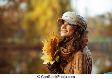 smiling woman with yellow leaves looking up at copy space