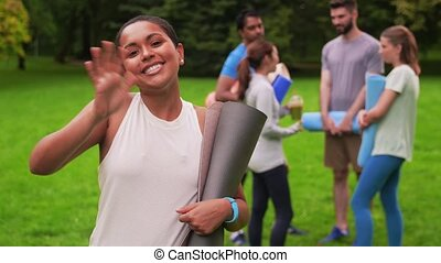 smiling woman with yoga mat over group of people - fitness, ...