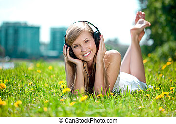 Smiling woman Woman listening to music on headphones...