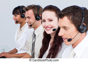 Smiling woman working in a call center with his colleagues