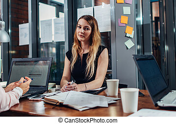 Smiling woman working sitting in modern office
