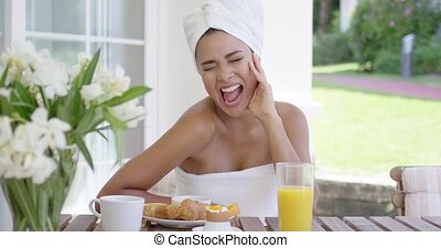 Smiling woman wrapped in towel having breakfast