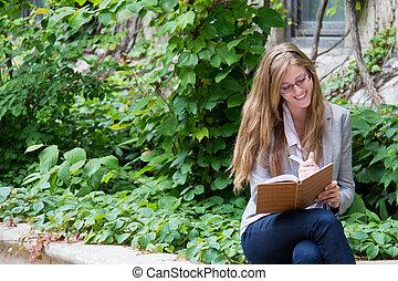 Smiling woman writes in her journal - Beautiful girl writing...