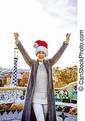 smiling womanin Santa hat at Guell Park in Barcelona...