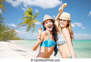 smiling women eating ice cream on beach