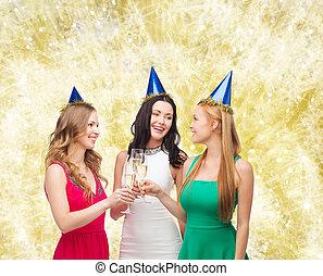 smiling women holding glasses of sparkling wine - drinks,...