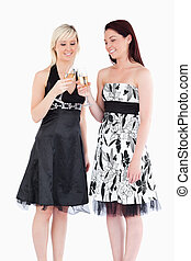 Smiling women in beautiful dresses toasting with champagne