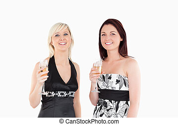Smiling women in dresses drinking champagne