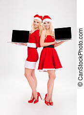 Smiling women in santa cloth showing blank laptop screen
