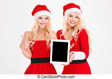 Smiling women in santa cloth showing tablet computer screen