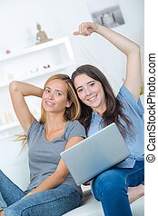 smiling women looking financial documents with laptop in home