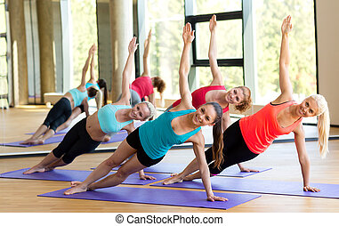 smiling women meditating on mat in gym - sport, meditation...