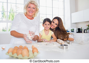 Smiling women of a family baking together