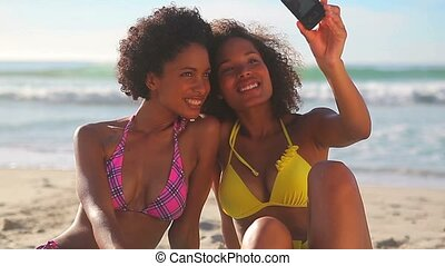 Smiling women photographing themselves on the beach