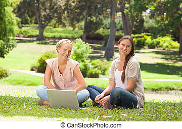 Smiling women sitting in the park with a laptop