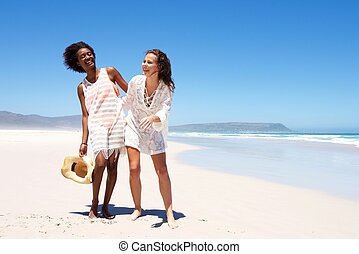 Smiling women walking together at the seaside