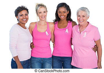 Smiling women wearing pink tops and breast cancer ribbons on...