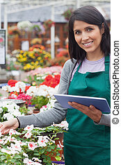 Smiling worker checking flowers in garden center