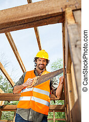 Smiling Worker Cutting Wood With Handsaw At Site