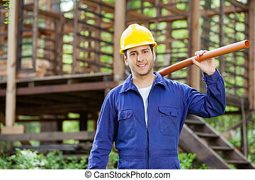Smiling Worker Holding Pipe At Construction Site