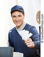 Smiling Worker Holding Tickets At Box Office - Portrait of...