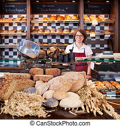 Smiling worker in the bakery - View across a display of a...