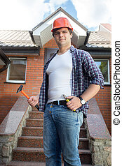Smiling worker posing in front of house with stone staircase