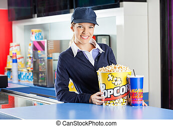 Smiling Worker With Snacks At Cinema Concession Counter