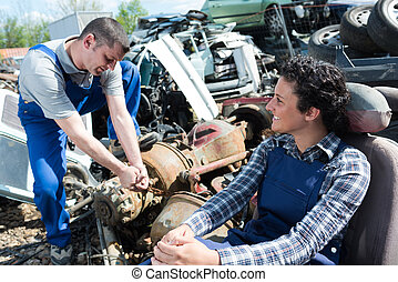 smiling workers in a junkyard