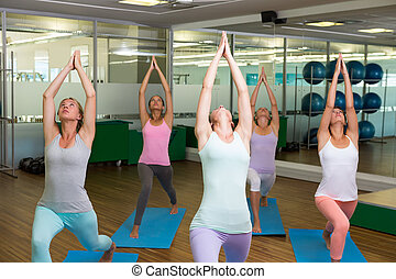 Smiling yoga class in fitness studio