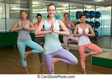 smiling yoga class in lotus pose in fitness studio at the