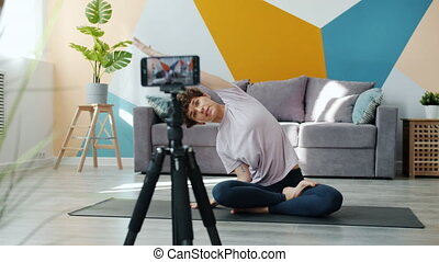 Smiling yoga instructor recording tutorial at home vlogging ...