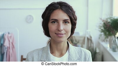 Smiling confident young adult female fashion designer, clothing store small business boutique owner, professional elegant millennial businesswoman dressmaker looking at camera. Close up portrait.