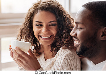 Smiling young African American couple drinking tea in the cafe