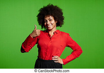 Smiling young African-American girl looking at camera gesturing thumb up