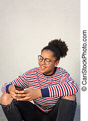 Smiling young african american girl sitting with mobile phone
