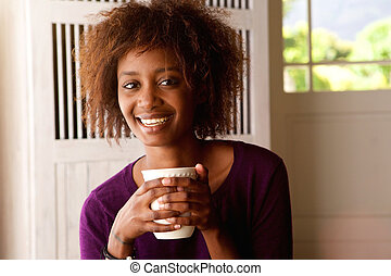 Smiling young african american woman drinking coffee