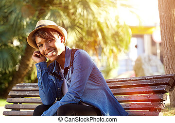 Smiling young african american woman sitting outside