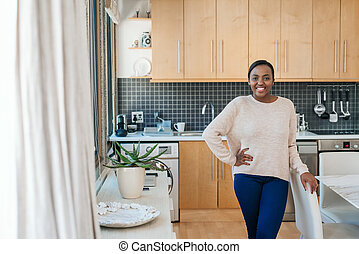 Smiling young African American woman standing in her apartment