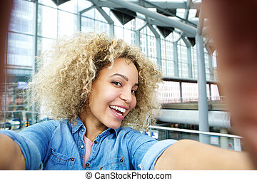 Smiling young african american woman taking selfie