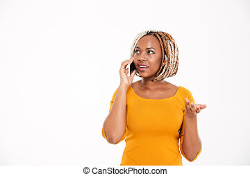 Smiling young african american woman talking on smartphone