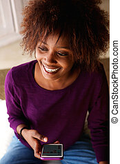 Smiling young african american woman with cell phone