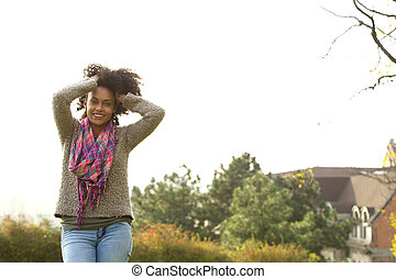 Smiling young african american woman with hands in hair