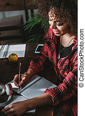 Smiling young african american woman writing in notebook at table